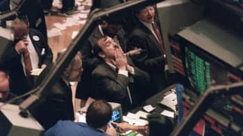 A trader (c) on the New York Stock Exchange looks at stock rates 19 October 1987 as stocks were devastated during one of the most frantic days in the exchange's history.