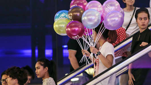 An employee holds branded balloons from Uniqlo as she rides on an escalator at the EmQuartier shopping mall in Bangkok, Thailand.