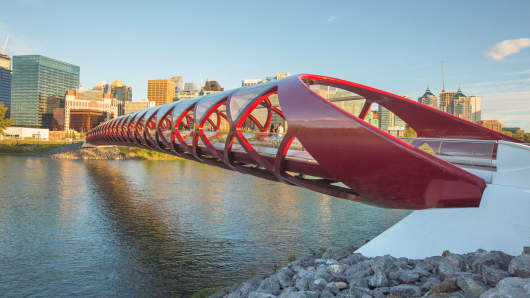 The iconic Peace Bridge spanning over the Bow River with Calgary's skyline in the background.