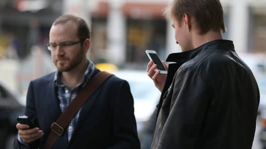 Two pedestrians use iPhones as they walk in Union Square in San Francisco, California.