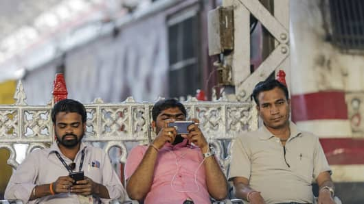 People use their smartphones at Mumbai Central railway station in Mumbai, India, where Google has rolled out high speed wi-fi that commuters can access for free.