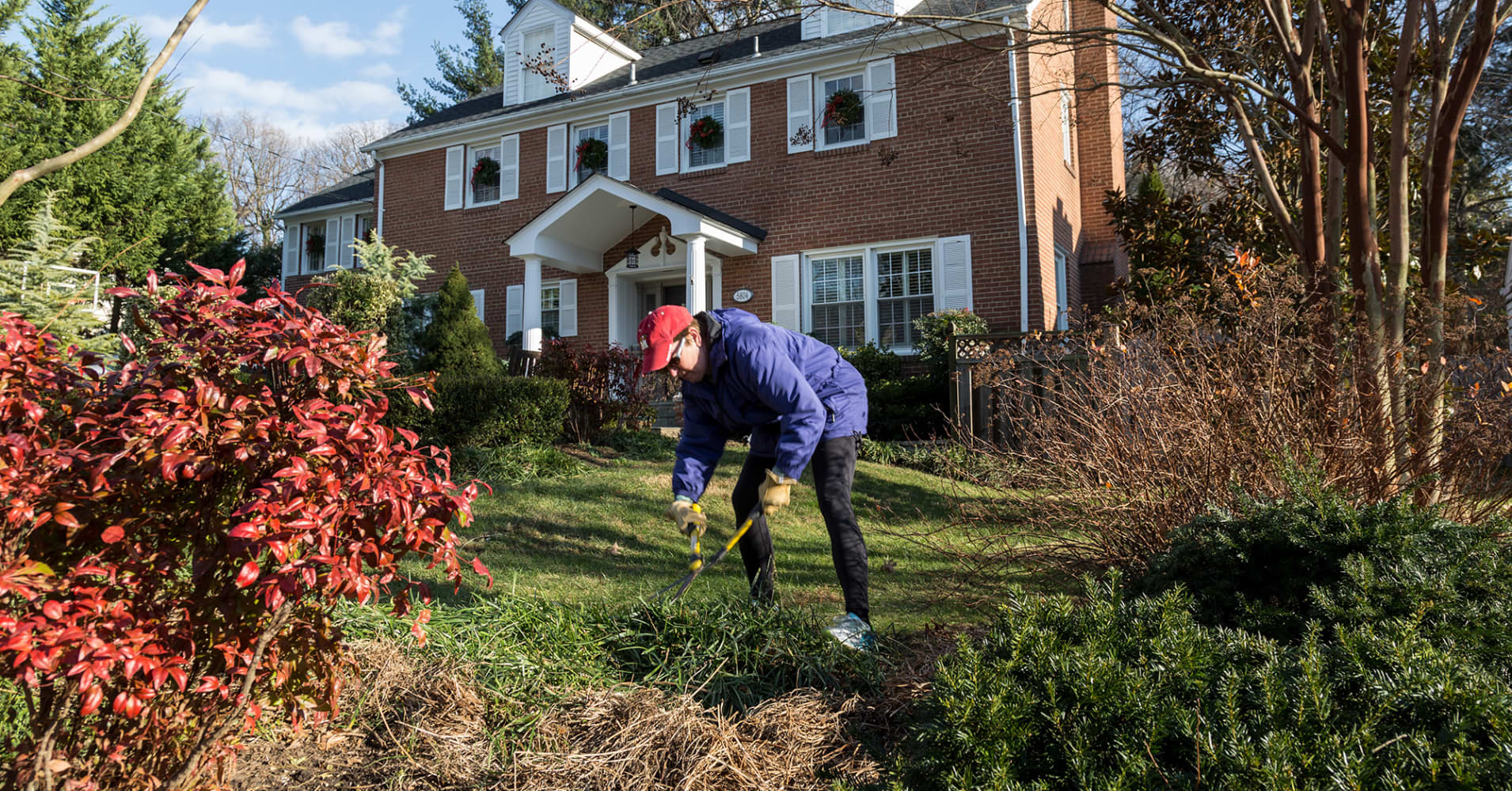 A homeowner trims her yard in the Kenwood Park neighborhood of Bethesda, Md.