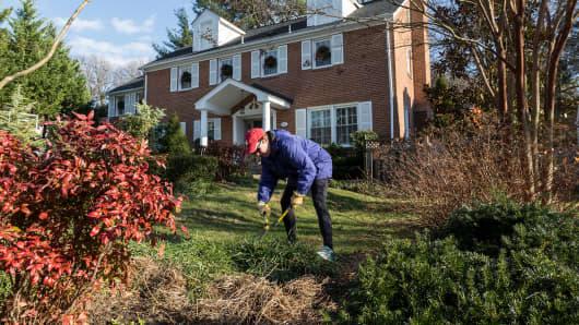 A homeowner trims her yard in the Kenwood Park neighborhood of Bethesda, Md.