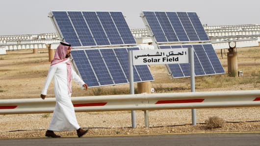 A Saudi man walks past a field of solar panels at the King Abdulaziz city of Sciences and Technology, Al-Oyeynah Research Station, in Saudi Arabia.