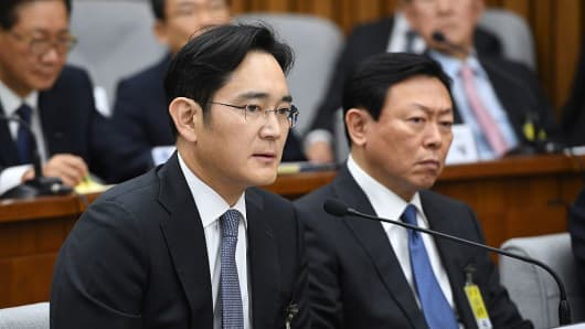 Samsung Group's heir-apparent Lee Jae-Yong (L) answers a question as Lotte Group Chairman Shin Dong-Bin (R) listens to during a parliamentary probe.