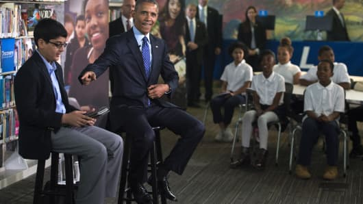 .S. President Barack Obama (R), with student moderator Osman Yaya (L), responds to a question during a 'Virtual Field Trip' with middle school students from around the country at Anacostia Library April 30, 2015 in Washington