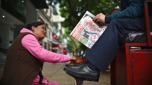 A bootblack polishes the shoes of a client who reads a newspaper with headlines referring to the eventual triumph of US presidential candidate Donald Trump on November 9, 2016 in Mexico City.