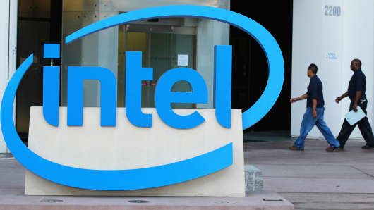 Intel employees walk by a sign as they enter their office in Santa Clara, California.