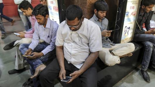 Passengers use their smartphones at Mumbai Central railway station in Mumbai, India, on January 22, 2016.