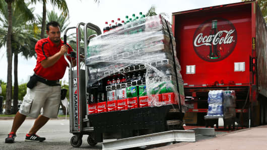 An employee delivers cases of Coca-Cola Co. brand soda in Miami Beach, Florida.