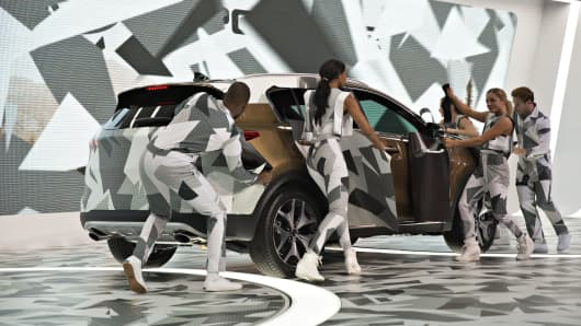 Performers remove a camouflage covering from a 2017 Kia Motors Sportage compact sports utility vehicle during its unveiling at the Los Angeles Auto Show on Wednesday, Nov. 18, 2015.