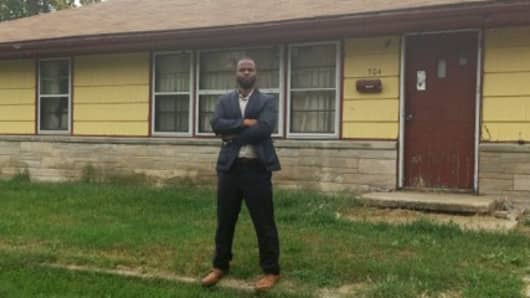 Bennie Smith stands in front of an investment property he bought in a tax lien sale.