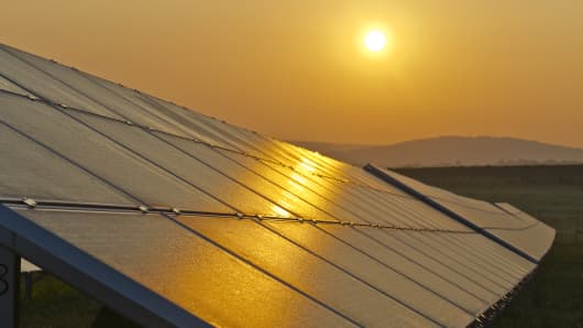 Photovoltaic solar panels in a row at sunrise.