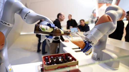 Robots in the Kuka stand pour a beer into a glass at the Hannover Messe industrial trade fair in Hanover, Germany April 23, 2016.