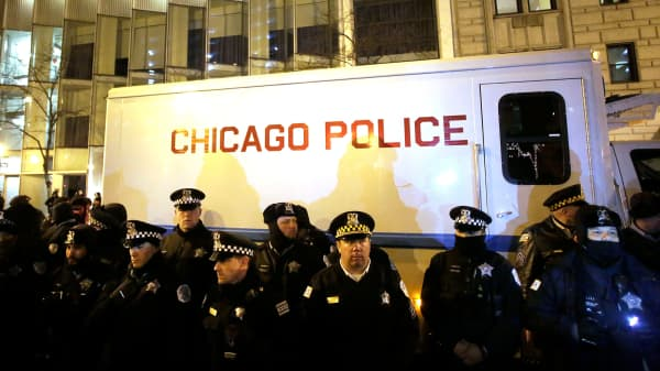 Chicago police officers surround a police vehicle as they watch demonstrators protesting the fatal police shooting of Laquan McDonald, December 18, 2015 in Chicago.