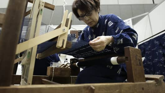 A craftworker operates a traditional Japanese textile weaving machine during a demonstration at the Monozukuri/Takumi no Waza Expo in Tokyo, Japan, on Wednesday, Aug. 10, 2016.