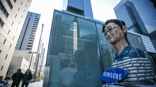 Pedestrians walk past an effigy of Jay Y. Lee, co-vice chairman of Samsung Electronics, outside Samsung's Seocho office building in Seoul, South Korea, on Friday, Jan. 13, 2017.
