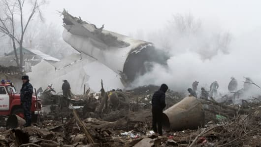 Rescue teams are seen at the crash site of Turkish cargo jet near Kyrgyzstan's Manas airport .