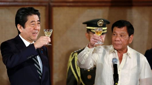 Philippine President Rodrigo Duterte (R) and Japanese Prime Minister Shinzo Abe (L) raise a toast during a state dinner at the Malacanang Presidential Palace in Manila on January 12, 2017.