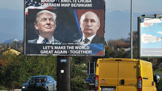 Cars pass by a billboard showing US President-elect Donald Trump and Russian President Vladimir Putin placed by pro-Serbian movement in the town of Danilovgrad on November 16, 2016.