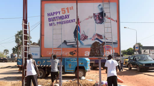 Workers prepare to remove an electoral poster of Gambia's outgoing president Yahya Jammeh on December 4, 2016.