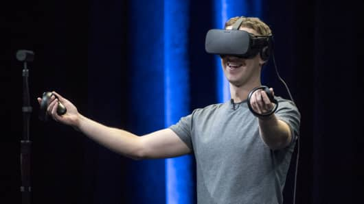 Mark Zuckerberg, chief executive officer and founder of Facebook Inc., demonstrates an Oculus Rift virtual reality (VR) headset and Oculus Touch controllers as the gives a demonstration during the Oculus Connect 3 event in San Jose, California