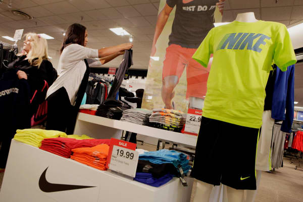 An employee folds Nike clothing in a J.C. Penney store.