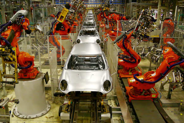 Robotic arms work on the bodyshells of Mini cars as they pass along a section of automated production line at the BMW Mini car production plant in Oxford, west of London.