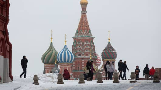 Pedestrians walk across Red Square past St. Basil's Cathedral in Moscow.