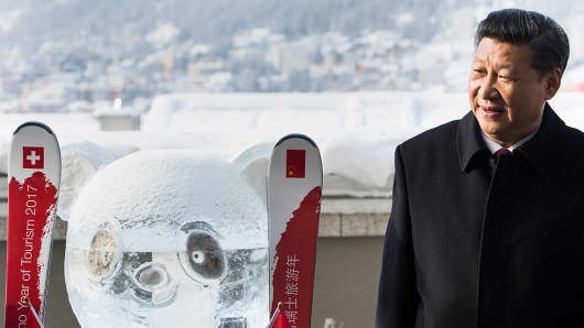 China's President Xi Jinping stands next to a panda ice sculpture while launching the Swiss-Sino year of tourism on the sidelines of the World Economic Forum in Davos.