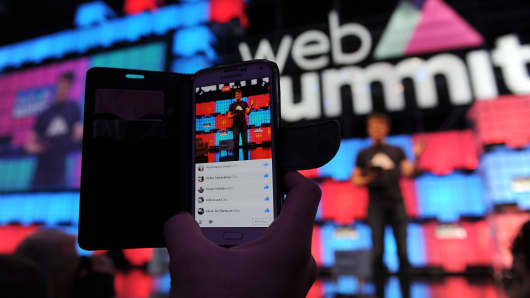 An attendee uses his mobile phone to film a Facebook Inc. Live video as Paddy Cosgrave, chief executive officer of Web Summit, speaks during the Lisbon Web Summit venue in Lisbon, Portugal, on Monday, Nov. 7, 2016.
