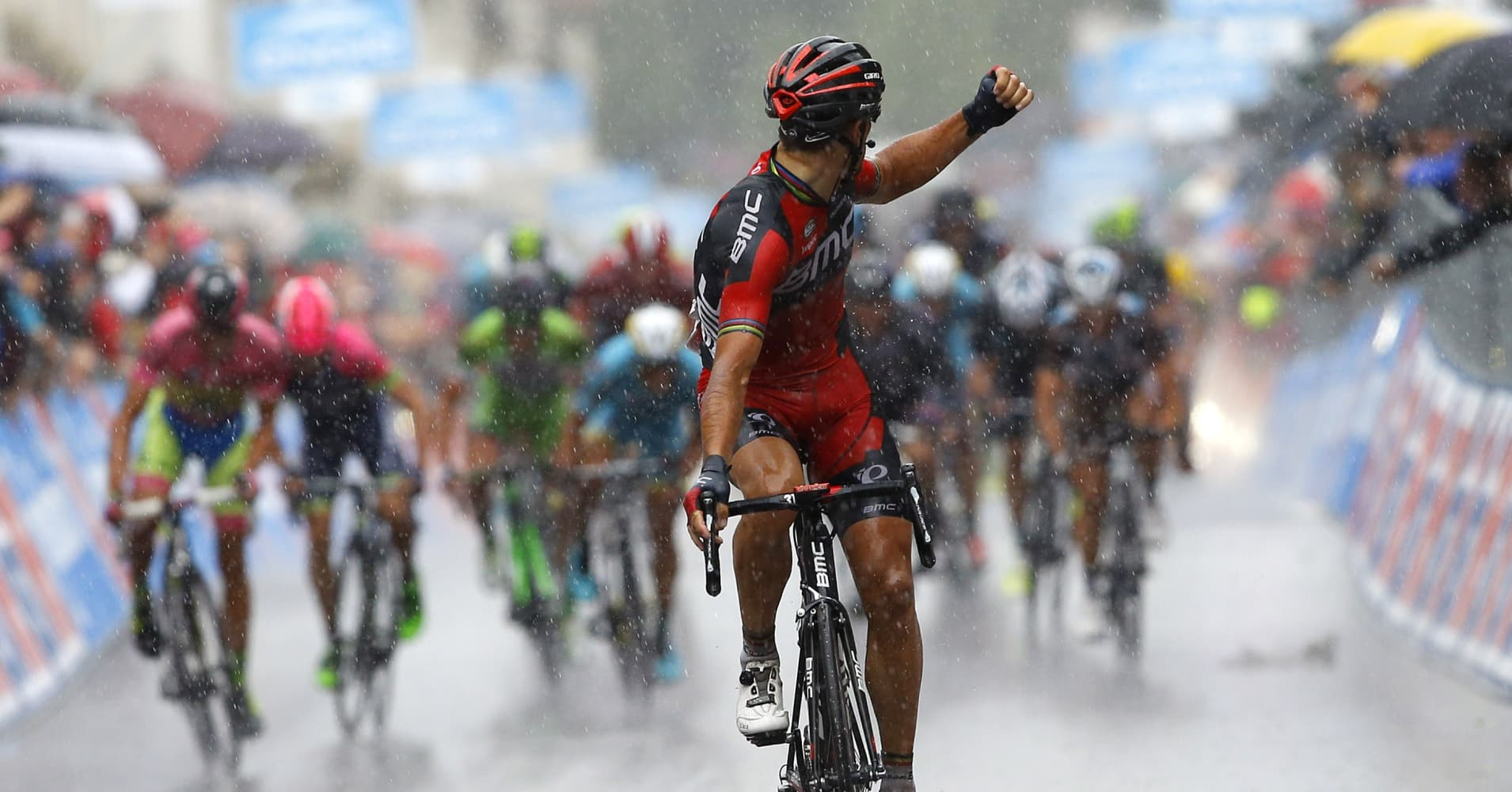 Belgian Philippe Gilbert of the BMC team celebrates as he crosses the finish line under heavy rain to win the 12th stage of the 98th Giro d'Italia, Tour of Italy, cycling race between Imola and Vicenza on May 21, 2015 in Vicenza.