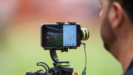 A television video person uses an iphone and stabilizer to film for facebook live broadcast before the game between the Syracuse Orange and the Louisville Cardinals on September 9, 2016 at The Carrier Dome in Syracuse, New York.