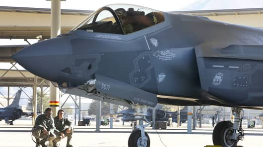 A fighter pilot sits in the cockpit while crew members check the exterior of a Lockheed Martin F-35A jet before a training flight in Hill Air Force Base, Utah, U.S., on Friday, Oct. 21, 2016.