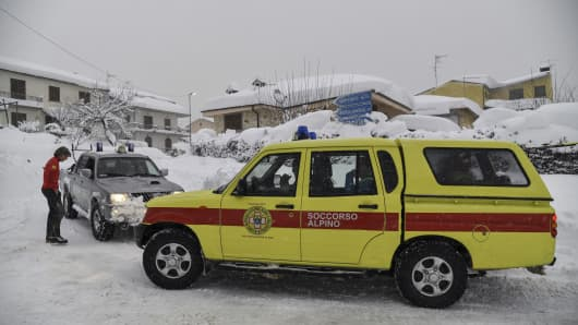 Emergency vehicles wait in the snow in Montereale's main street, near Amatrice, after a 5.7-magnitude earthquake struck the region, on January 18, 2017.