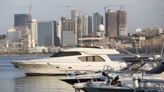 Luxury motor yachts sit at their harbor moorings in Ilha district beyond the city center skyline in Luanda, Angola