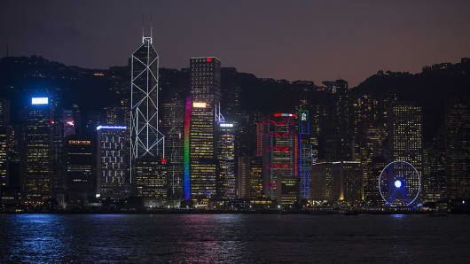 Buildings stand illuminated along Victoria Harbour at night in Hong Kong, China, on Friday, Nov. 4, 2016