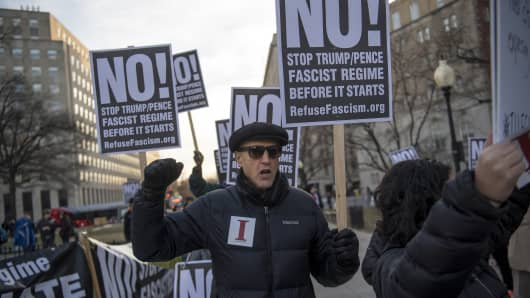 Protesters hold signs while demonstrating at McPherson Square in Washington, D.C., on Thursday, Jan. 19, 2017.