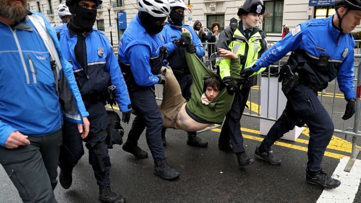 A protester is dragged away from a public access point to the National Mall on 14th Street NW prior to the inauguration on January 20, 2017 in Washington, DC.