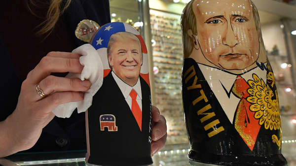 An employee polishes traditional Russian wooden nesting dolls, Matryoshka dolls, depicting US President-elect Donald Trump (L) and Russian President Vladimir Putin at a gift shop in central Moscow.
