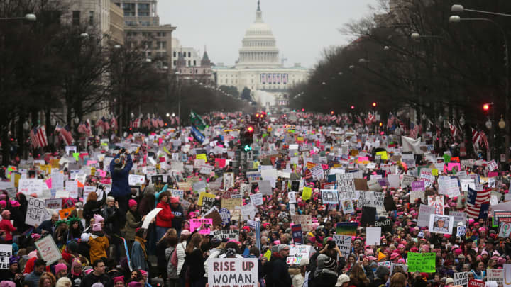 Protesters walk during the Women's March on Washington, with the U.S. Capitol in the background, on January 21, 2017 in Washington, DC.
