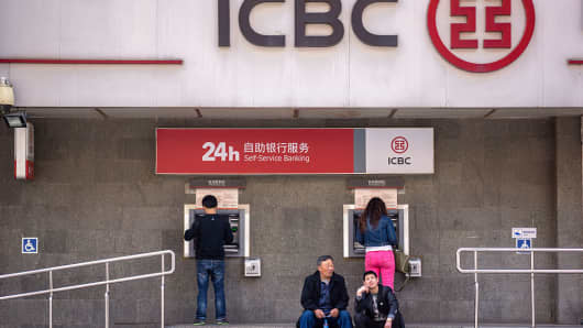 People withdraw money from an ICBC branch in Beijing.
