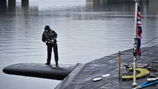Royal Navy security personnel stand guard on Trident submarine HMS Vigilant in Scotland.