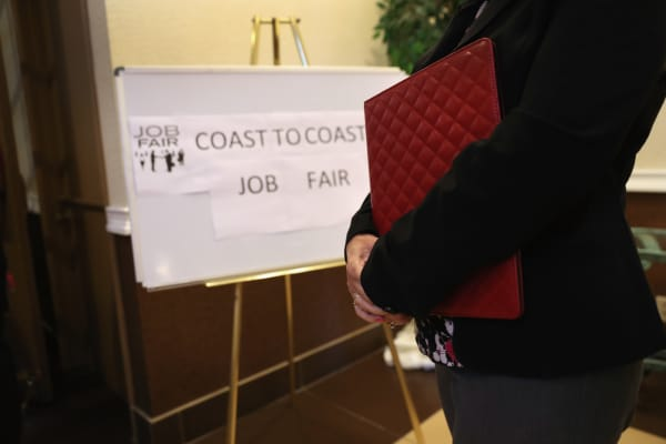 A woman waits to meet potential employers at a job fair