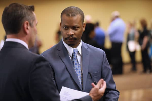 A man speaks with potential employer at a job fair