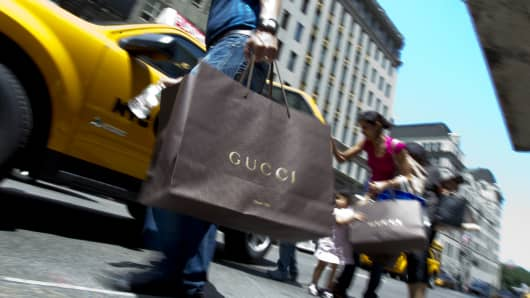 Shoppers holding Gucci shopping bags enter a taxi on Fifth Avenue in New York.