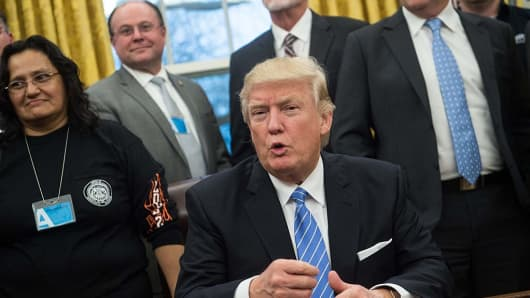 U.S. President Donald Trump speaks as he poses with labor leaders on January 23, 2017 in the Oval Office at the White House in Washington, DC.