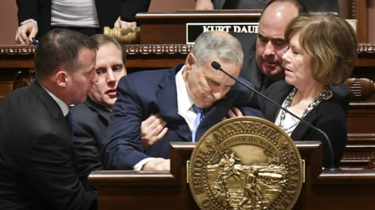 Minnesota Lt. Governor Tina Smith, right, and Secretary of State Steve Simon, left, help Minnesota Gov. Mark Dayton after he collapsed during his State of the State address in St. Paul, Minn., Monday, Jan. 23, 2017.