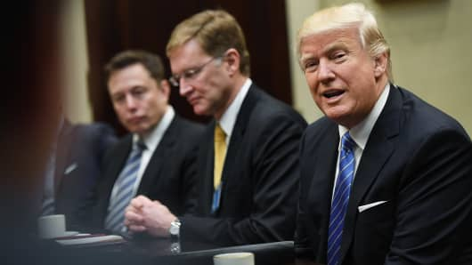 Elon Musk, left, and Wendell P. Weeks, center, listen to President Donald Trump as he meets with business leaders at the White House on Monday January 23, 2017 in Washington, DC.