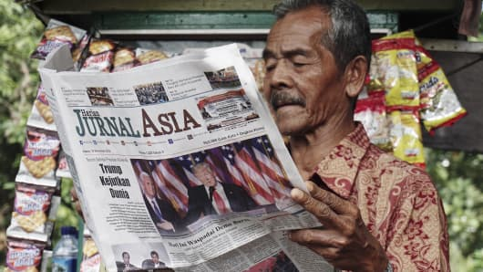 An Indonesian man reads a newspaper featuring an article about US President-elect Donald Trump at a stall on November 10, 2016 in Medan, Indonesia.
